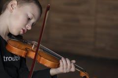 Βιολί λαβής λαβών Φέρνοντας βιολί μικρών παιδιών Νέο βιολί παιχνιδιού αγοριών, ταλαντούχος φορέας βιολιών στοκ φωτογραφίες με δικαίωμα ελεύθερης χρήσης