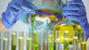 Βιοχημικός που στάζει την κίτρινη ουσία στο σωλήνα δοκιμής με τις πράσινες εγκαταστάσεις, εξαγωγή απόθεμα βίντεο