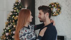 Βλασταημένος από κοντά μακριά ενός γοητευτικού ζεύγους yound ερωτευμένου huging ο ένας τον άλλον στο υπόβαθρο χριστουγεννιάτικων  απόθεμα βίντεο