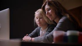 Βλαστός κινηματογραφήσεων σε πρώτο πλάνο της νέας καυκάσιας μητέρας με μια μικρή όμορφη κόρη που προσέχει κινούμενα σχέδια μαζί κ απόθεμα βίντεο