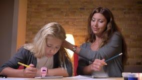 Βλαστός κινηματογραφήσεων σε πρώτο πλάνο της νέας καυκάσιας μητέρας που βοηθά τη μικρή όμορφη κόρη της με τα ομιλούντα και καθορί φιλμ μικρού μήκους
