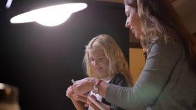 Βλαστός κινηματογραφήσεων σε πρώτο πλάνο της νέας καυκάσιας μητέρας που διδάσκει τη μικρή όμορφη κόρη της στο σπίτι απόθεμα βίντεο