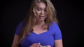 Βλαστός κινηματογραφήσεων σε πρώτο πλάνο του μέσου ηλικίας καυκάσιου θηλυκού χρησιμοποιώντας το τηλέφωνο και εξετάζοντας τη κάμερ απόθεμα βίντεο