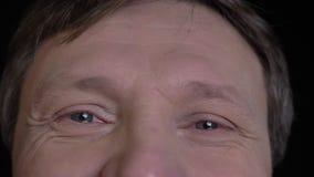 Βλαστός κινηματογραφήσεων σε πρώτο πλάνο του μέσου ηλικίας καυκάσιου αρσενικού προσώπου με τα γκρίζα μάτια που εξετάζουν ευθέα τη απόθεμα βίντεο