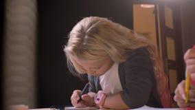 Βλαστός κινηματογραφήσεων σε πρώτο πλάνο του νέου αρκετά ξανθού κοριτσιού που κάνει την εργασία της στην παρουσία γονέα απόθεμα βίντεο