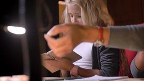 Βλαστός κινηματογραφήσεων σε πρώτο πλάνο του διέγερσης της μικρής όμορφης μαθήτριας που καλύπτει την εργασία της και με το υπόβαθ απόθεμα βίντεο