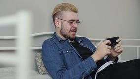Βλαστός τρόπου ζωής του νέου ελκυστικού millenial ατόμου με το μοντέρνο παίζοντας παιχνίδι κουρέματος στο smartphone στο άσπρο κρ φιλμ μικρού μήκους