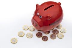 Βρετανικά χρήματα, νομίσματα λιβρών με την κόκκινη piggy τράπεζα στοκ φωτογραφία