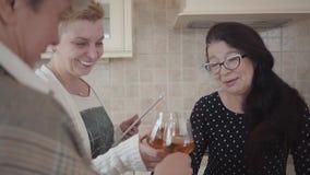 Γέλιο τριών καλό ανώτερο γυναικών έξω δυνατό μαζί ενώ πίνοντας κρασί, μια ταμπλέτα εκμετάλλευσης στα χέρια Μέσος ηλικίας ώριμος απόθεμα βίντεο