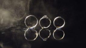 Γαμήλια δαχτυλίδια και δαχτυλίδι αρραβώνων που βρίσκονται στη σκοτεινή επιφάνεια νερού που λάμπει με το φως Κλείστε επάνω τη μακρ απόθεμα βίντεο