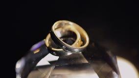 Γαμήλια δαχτυλίδια που βρίσκονται στο κρύσταλλο που λάμπει με την ελαφριά στενή επάνω μακροεντολή Μαύρη ανασκόπηση κίνηση αργή φιλμ μικρού μήκους