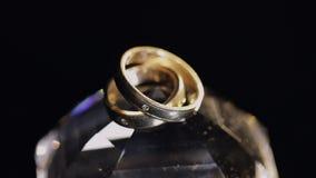 Γαμήλια δαχτυλίδια που βρίσκονται στο κρύσταλλο που λάμπει με την ελαφριά στενή επάνω μακροεντολή Μαύρη ανασκόπηση κίνηση αργή απόθεμα βίντεο