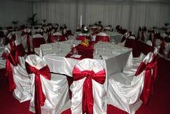 Γαμήλια ρύθμιση με τις άσπρες και κόκκινες καρέκλες που περιμένει τους φιλοξενουμένους γ στοκ εικόνα με δικαίωμα ελεύθερης χρήσης