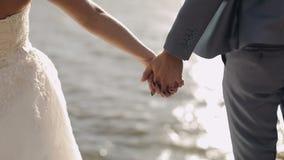 Γαμήλιο ζεύγος μαζί στην κλίση του βουνού κοντά στη θάλασσα Ο νεόνυμφος παίρνει το χέρι νυφών κίνηση αργή κλείστε επάνω Λίγοι πυρ απόθεμα βίντεο