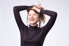 Γελώντας γυναίκα με μακρυμάλλη πέρα από τον άσπρο τοίχο στοκ φωτογραφίες