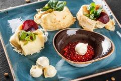Γεμισμένος crepes ολοκληρωμένος με το κόκκινο χαβιάρι, το βούτυρο και τα πράσινα στο πιάτο Άποψη σχετικά με μια σκοτεινή γκρίζα ε στοκ εικόνες