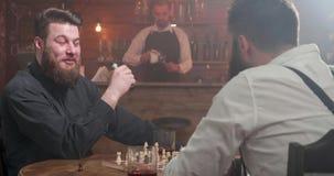 Γενειοφόρα hipsters που έχουν μια συνομιλία σε έναν φραγμό παίζοντας το σκάκι απόθεμα βίντεο