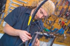 Γενειοφόρος τύπος που επισκευάζει το ποδήλατο στο εργαστήριο στοκ εικόνες