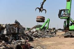 Γερανοί που επεξεργάζονται το απορριμμένο μέταλλο σιδήρου απορρίματος σε ένα ανακυκλώνοντας κέντρο παλιοσίδερου στοκ εικόνες