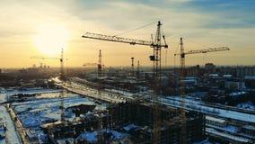 Γερανοί πύργων στην εργασία σε ένα εργοτάξιο οικοδομής κοντά στο ατελές κτήριο απόθεμα βίντεο
