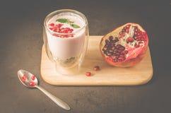γιαούρτι Γιαούρτι με τα δημητριακά, το γρανάτη και τη μέντα στο γυαλί και τα φρούτα ροδιών σε έναν ξύλινο δίσκο Σκοτεινός πίνακας στοκ φωτογραφίες με δικαίωμα ελεύθερης χρήσης