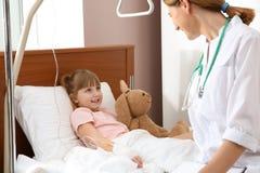 Γιατρός που επισκέπτεται λίγο παιδί με την ενδοφλέβια σταλαγματιά στοκ εικόνα