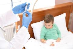 Γιατρός που ρυθμίζει την ενδοφλέβια σταλαγματιά για λίγο παιδί στο νοσοκομείο στοκ εικόνα