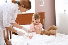 Γιατρός που ρυθμίζει την ενδοφλέβια σταλαγματιά για λίγο παιδί στοκ εικόνα