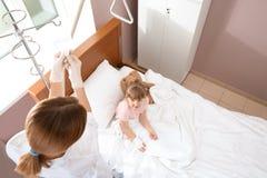 Γιατρός που ρυθμίζει την ενδοφλέβια σταλαγματιά για λίγο παιδί στο νοσοκομείο στοκ φωτογραφίες με δικαίωμα ελεύθερης χρήσης