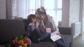 Γιος που παρουσιάζει στη ευχετήρια κάρτα mom και το κιβώτιο δώρων απόθεμα βίντεο