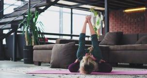 Γιόγκα άσκησης γυναικών καθιστικών ρετηρέ το πρωί για να έχει ένα υγιές σώμα, αυτή που τεντώνει πριν από την έναρξη α απόθεμα βίντεο