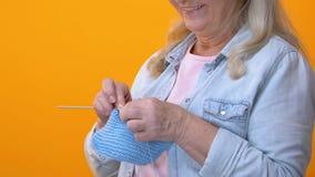 Γκρίζος-μαλλιαρό πλέξιμο γιαγιάδων στο κίτρινο υπόβαθρο, χόμπι τεχνών, αποχώρηση απόθεμα βίντεο