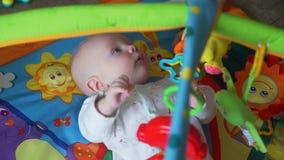 Γλυκό παιχνίδι μωρών με τα παιχνίδια στο χαλί φιλμ μικρού μήκους