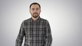 Γοητεία του επιτυχούς νέου επιχειρηματία στο περπάτημα και το κοίταγμα στις πλευρές στο υπόβαθρο κλίσης απόθεμα βίντεο