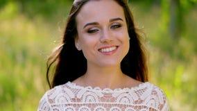 Γοητευτική γυναίκα χαμόγελα στα άσπρα φορεμάτων στη κάμερα Κινηματογράφηση σε πρώτο πλάνο φιλμ μικρού μήκους
