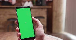 Γρήγορα κινούμενο parallax που πυροβολείται του τηλεφώνου με την πράσινη οθόνη στην επίδειξη φιλμ μικρού μήκους