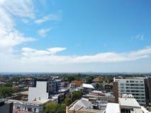 Γραμμή τοπίου πόλεων κάτω από το μπλε ουρανό και τα άσπρα σύννεφα στοκ εικόνες