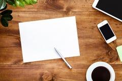 Γραφείο εργασίας με το άσπρο κενό φύλλο εγγράφου για τη μάνδρα και τις συσκευές σημειώσεων στοκ φωτογραφία με δικαίωμα ελεύθερης χρήσης