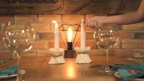 Γυαλί κρασιού που στέκεται στον εξυπηρετούμενο πίνακα γευμάτων με το κάψιμο του κεριού για τη ρομαντική ημερομηνία στο εστιατόριο απόθεμα βίντεο