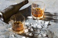 Γυαλιά με τους κύβους πάγου κονιάκ και λειωμένων μετάλλων, μπουκάλι στο μετρητή φραγμών στοκ εικόνες με δικαίωμα ελεύθερης χρήσης