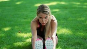 Γυναίκα αθλητών που κάνει την άσκηση τεντωμάτων πριν από την κατάρτιση ικανότητας στο θερινό πάρκο απόθεμα βίντεο