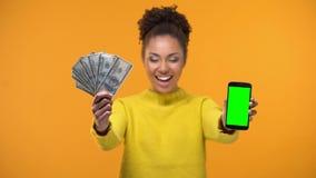 Γυναίκα αφροαμερικάνων που παρουσιάζει το smartphone και δέσμη των δολαρίων, μεταφορά χρημάτων απόθεμα βίντεο