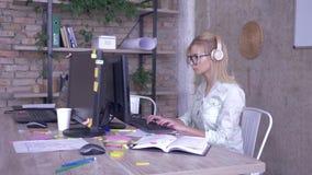 Γυναίκα εργαζόμενος στα γυαλιά και τα ακουστικά που λειτουργούν στο προσωπικό Η/Υ σε ένα σύγχρονο δημιουργικό γραφείο απόθεμα βίντεο