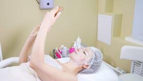 Γυναίκα με μια μάσκα στο πρόσωπό της που χρησιμοποιεί το τηλέφωνό της κάνοντας τον καλλυντικό καθαρισμό διαδικασιών mesotherapy τ απόθεμα βίντεο
