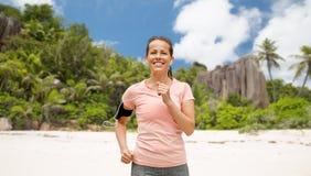 Γυναίκα με τα ακουστικά και armband που τρέχει στην παραλία στοκ φωτογραφία