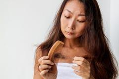 Γυναίκα με την τρίχα και τη χτένα υπό εξέταση Έννοια απώλειας τρίχας στοκ εικόνα με δικαίωμα ελεύθερης χρήσης