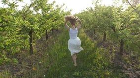 Γυναίκα με την πετώντας τρίχα που τρέχει την άνοιξη τον οπωρώνα απόθεμα βίντεο