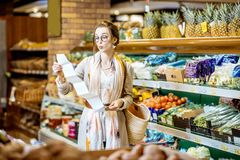 Γυναίκα με το μακρύ κατάλογο αγορών στην υπεραγορά στοκ φωτογραφία με δικαίωμα ελεύθερης χρήσης