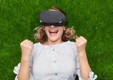 Γυναίκα στη νίκη εορτασμού κασκών VR στη χλόη στοκ φωτογραφία με δικαίωμα ελεύθερης χρήσης