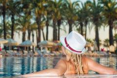 Γυναίκα στη χαλάρωση καπέλων στην πισίνα Κορίτσι travel spa στη λίμνη θερέτρου Διακοπές θερινής πολυτέλειας στοκ εικόνες